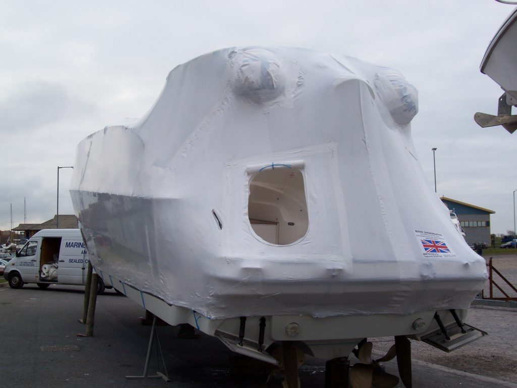 A shrink wrapped boat with a zip entrance door