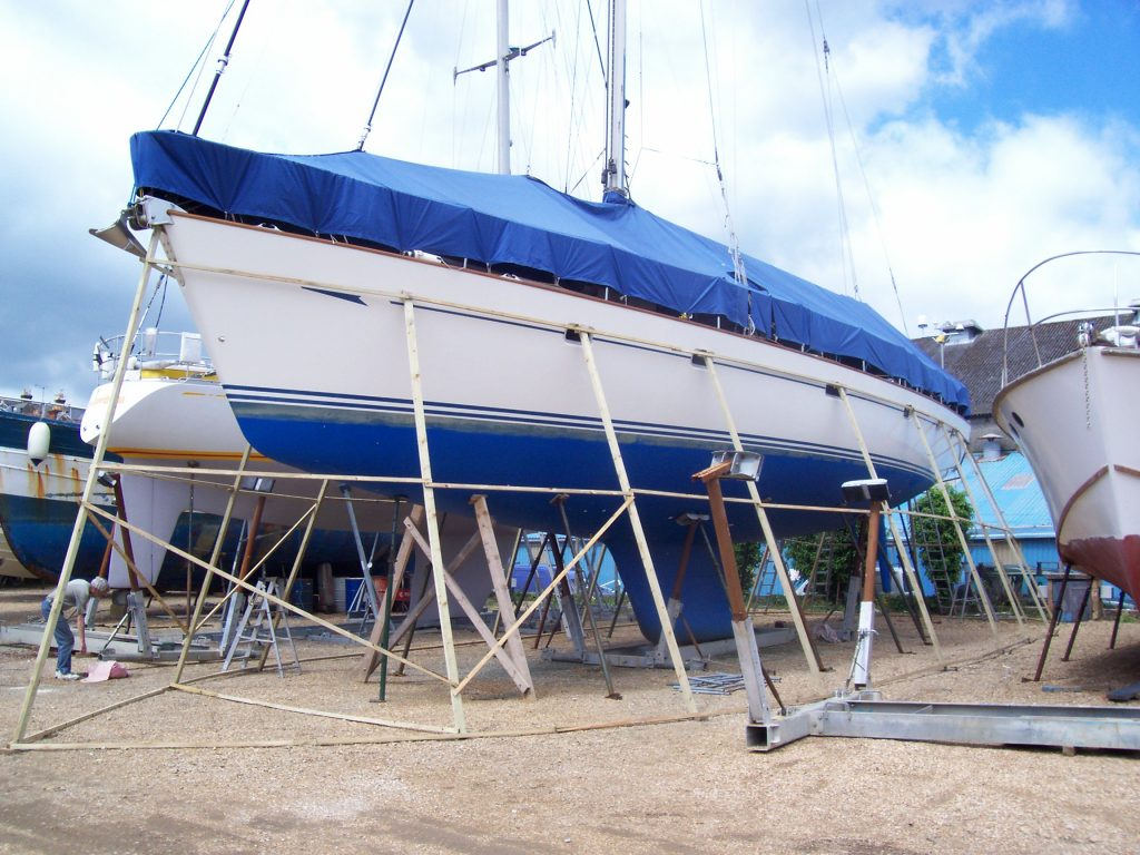 Yacht whose hull is being prepared for containment with shrink wrap and timber